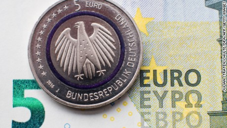 "Illustration taken on April 14, 2016 in Hanover, central Germany, shows a five-euro collector coin titled ""Planet Earth"" in front of a five-euro banknote. From now on, the coin is available at branches of the Deutsche Bundesbank (German Central Bank) and many other banks. As the Bundesbank explains on its internet site, ""The coin consists of three components  an outer ring depicting the cosmos, with numerous planets; an inner core portraying Earth; and a blue polymer ring holding both metal components together. The polymer ring, which shines blue when held up to the light, visually represents the link between Earth and the cosmos"". / AFP / dpa / Julian Stratenschulte / Germany OUT        (Photo credit should read JULIAN STRATENSCHULTE/AFP/Getty Images)"
