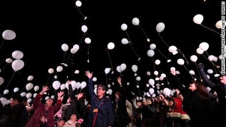 People release balloons, carrying their wishes, to celebrate the New Year at Prince Park Tower in the Japanese capital Tokyo on January 1, 2017. / AFP / Behrouz MEHRI        (Photo credit should read BEHROUZ MEHRI/AFP/Getty Images)