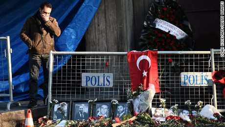 A friend of a victim mourns next to victims pictures in front of the Reina nightclub on January 2, 2017  in Istanbul, one day after a gunman killed 39 people, including many foreigners, in a rampage at an upmarket nightclub in Istanbul where revellers were celebrating the New Year. The shooting spree at the waterside Reina nightclub was unleashed when 2017 in Turkey was just 75 minutes old, after a year of unprecedented bloodshed that saw hundreds of people die in strikes blamed on jihadists and Kurdish militants and a bloody failed coup. / AFP / OZAN KOSE        (Photo credit should read OZAN KOSE/AFP/Getty Images)
