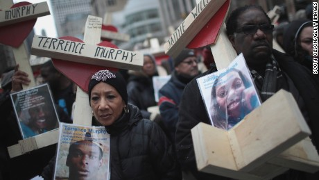 CHICAGO, IL - DECEMBER 31:  Residents, activists, and friends and family members of victims of gun violence march down Michigan Avenue carrying nearly 800 wooden crosses bearing the names of people murdered in the city in 2016 on December 31, 2016 in Chicago, Illinois. Nearly 800 people have been murdered in the city this year and more than 4000 shot as the city copes with its most violent year in two decades.  (Photo by Scott Olson/Getty Images)