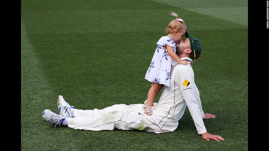 Cricket player Nathan Lyon celebrates with his daughter Friday, December 30, after Australia defeated Pakistan in a Test match in Melbourne.