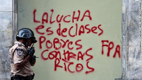 "A policeman walks past a graffiti reading ""The fight is of poor and rich classes"" outside the National Assembly ahead of  Venezuelan president Nicolas Maduro's presentation of the annual report before the opposition controlled parliament in Caracas on January 15, 2016. Maduro decreed a two-month state of ""economic emergency"" Friday, seizing the initiative ahead of a key showdown in his standoff with the opposition in the oil-rich nation. AFP PHOTO/RONALDO SCHEMIDT / AFP / RONALDO SCHEMIDT        (Photo credit should read RONALDO SCHEMIDT/AFP/Getty Images)"