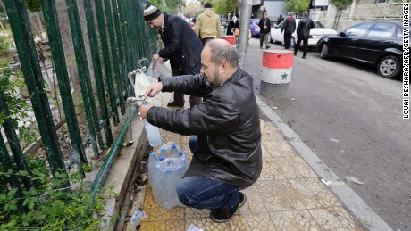 Damascus residents fill plastic containers with water at a public fountain.