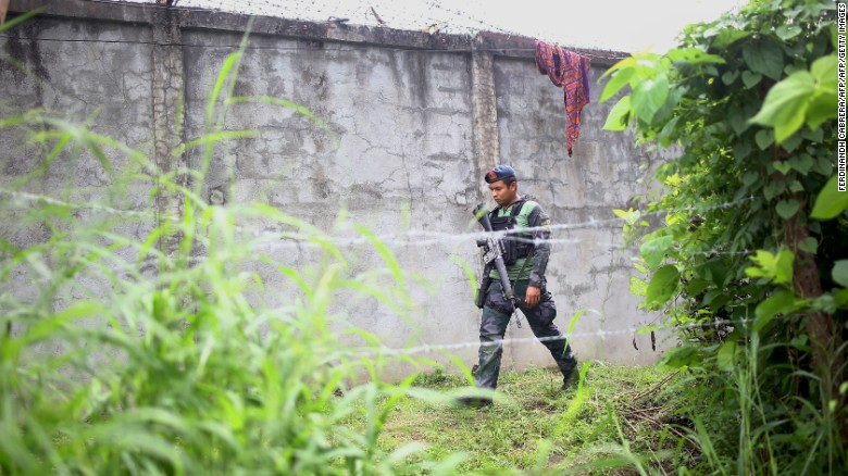 An armed policeman patrols along the perimeter fence of the North Catobato district jail, from which more than 150 inmates escaped.