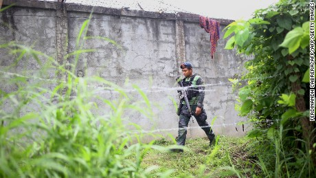 An armed policeman patrols along a perimeter fence.