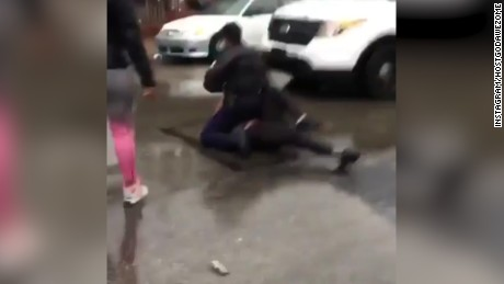 A still image from a video shows the unidentified officer on top of the teen.