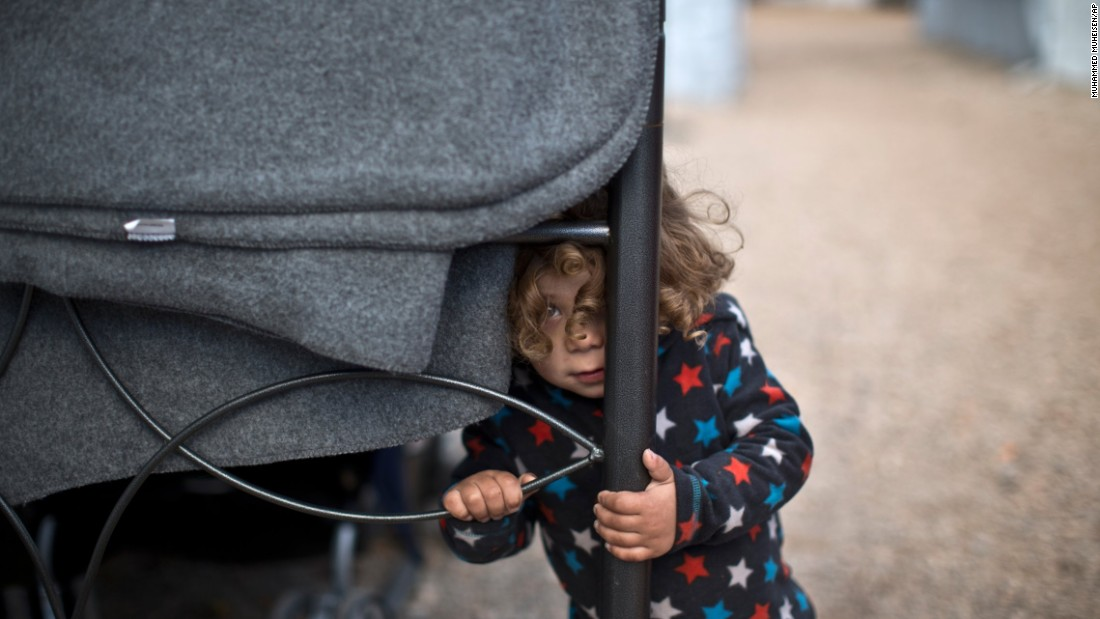 Moustafa Abdulrahman, a 2-year-old Syrian refugee, peeks outside his family's shelter at the Ritsona camp in Greece on Thursday, January 5. More than 60,000 migrants are stranded in Greece after a series of Balkan border closures and a European Union deal with Turkey.
