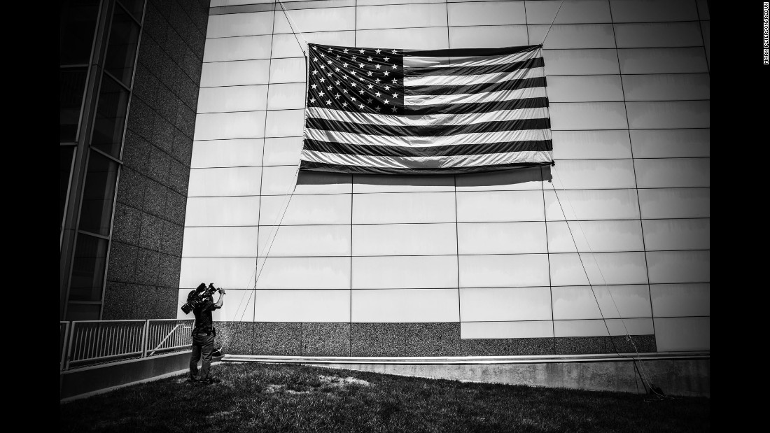 A cameraman films a large American flag outside the Republican National Convention.