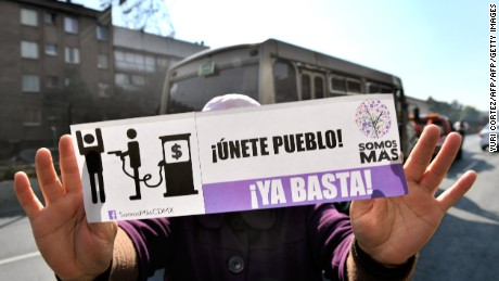 Activists hold signs and shout slogans against the rise in fuel prices while blocking a gas station along Tlalpan avenue during a protest in Mexico City on January 3, 2017.  Mexicans angry over a steep hike in gasoline prices blocked roads around the country Monday, but the government refused to budge on the energy reform behind the increase. / AFP / YURI CORTEZ        (Photo credit should read YURI CORTEZ/AFP/Getty Images)