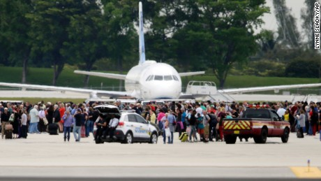 People stand on the tarmac at the Fort Lauderdale-Hollywood International Airport after a lone shooter opened fire inside the terminal, Friday, January 6, in Fort Lauderdale, Florida.