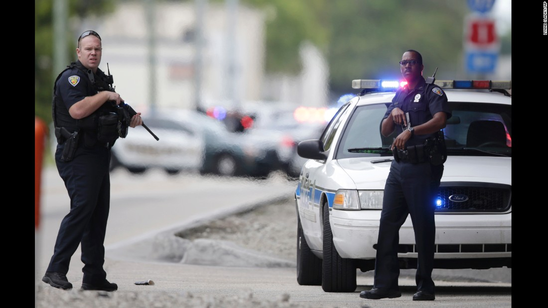 Police officers stand on the perimeter road at the Fort Lauderdale-Hollywood International Airport.