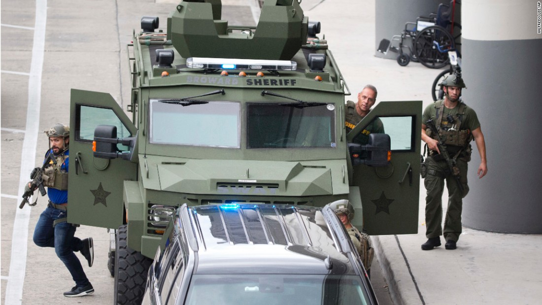 Law enforcement personnel arrive in an armored car outside the airport.
