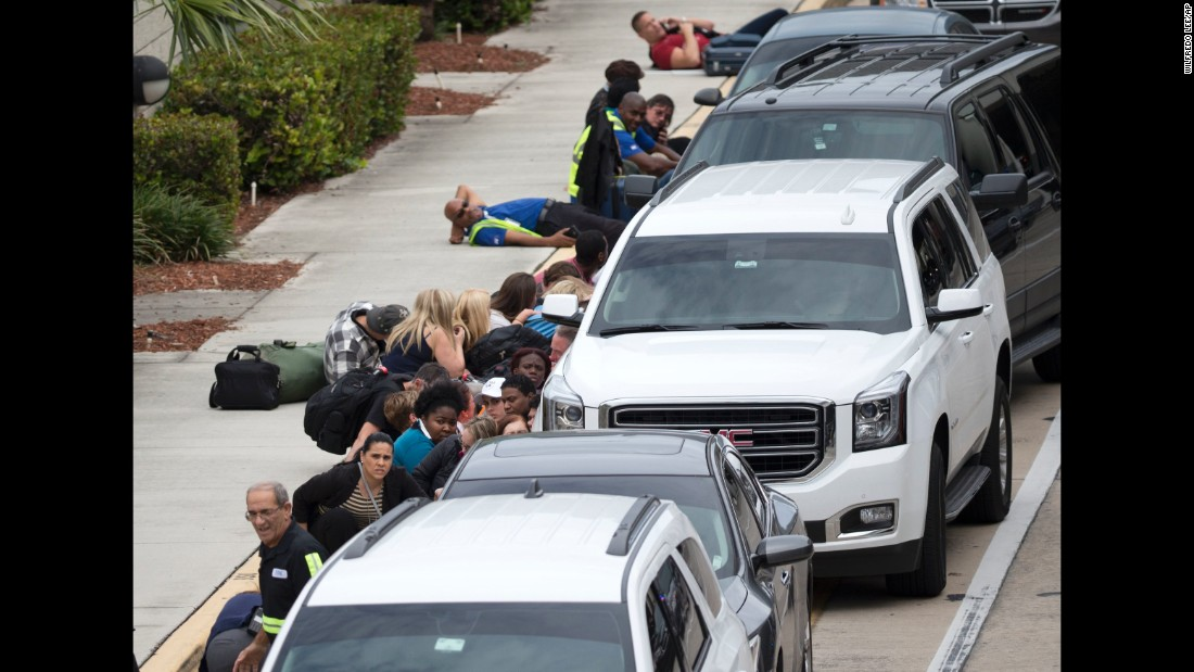 People take cover outside the airport in the chaos following the shooting.