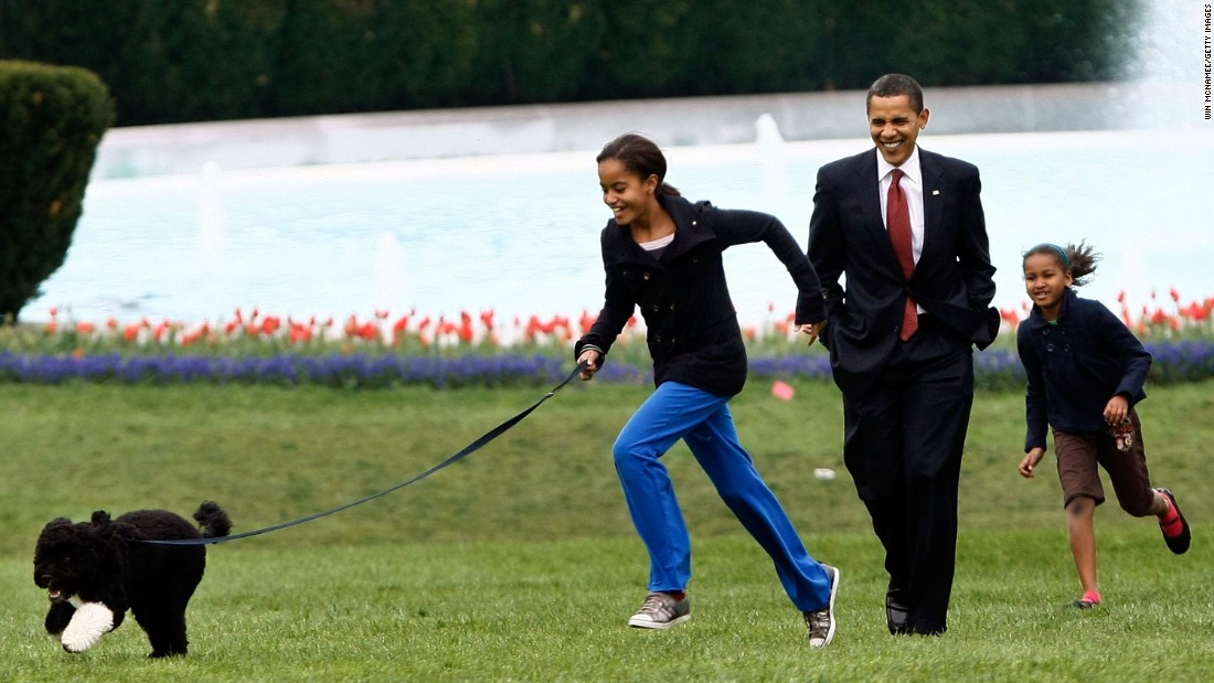 "The President takes Malia, left, and Sasha for a walk <a href=""http://www.cnn.com/2009/POLITICS/04/14/first.dog/"">with their new dog, Bo,</a> on the South Lawn of the White House in April 2009. The Portuguese water dog was a gift from Sen. Edward Kennedy. The first family chose the purebreed puppy largely because of Malia's allergies."