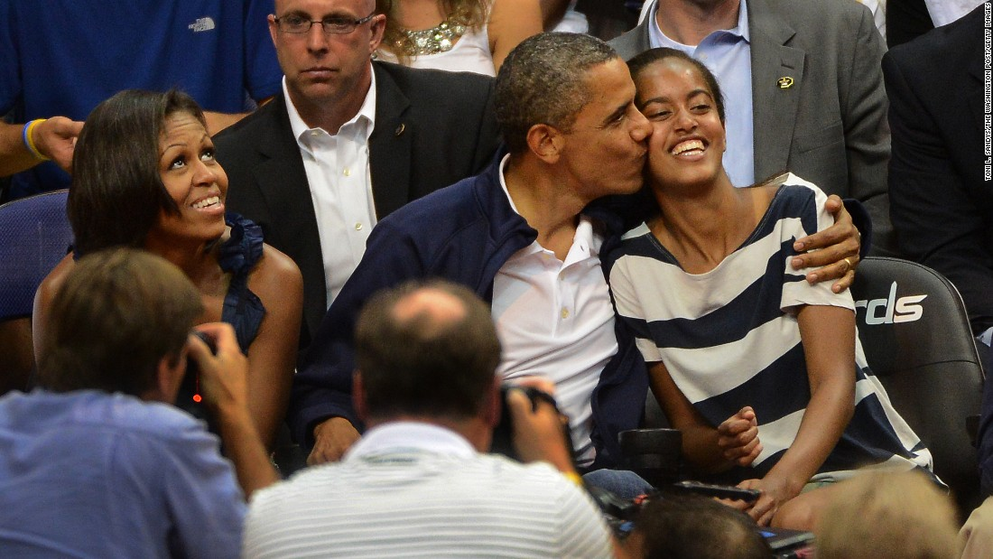 "Obama gives Malia a hug and a kiss after not kissing his wife, Michelle, on the ""Kiss Cam"" at the Verizon Center in July 2012."