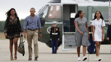 President Barack Obama with first lady Michelle Obama and their daughters Malia, right, and Sasha, left, walk on the tarmac to board Air Force One at Air Station Cape Cod in Massachusetts on August 21, 2016.