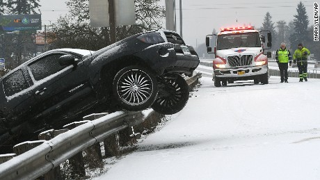 An ODOT and an AA Towing employee work on the removal of a Toyota pickup laying over a guardrail in Albany, Oregon on January 7. A few hours of freezing rain followed by a dusting of snow created havoc to drivers on the Interstate.