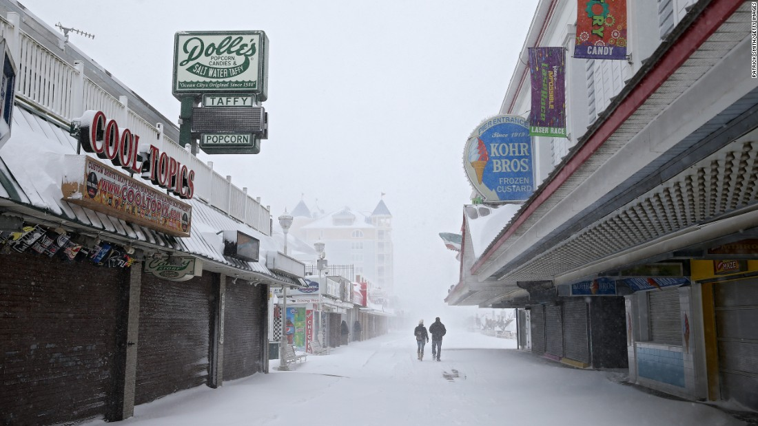 People walk on the boardwalk on January 7 in Ocean City, Maryland. The storm dumped more than eight inches of snow on Maryland's lower Eastern Shore.