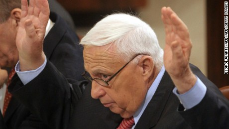 Israeli Prime Minister Ariel Sharon raises his hand while voting for a bill to compensate settlers leaving Gaza.