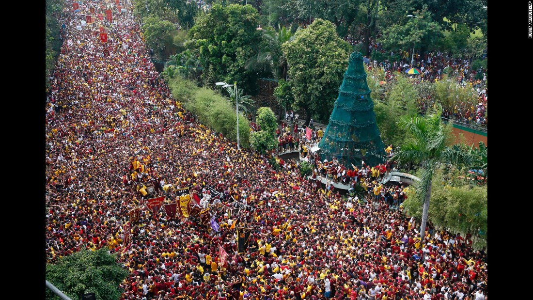 Filipino Roman Catholic devotees climb the carriage to kiss the image of the Black Nazarene during a procession to celebrate its feast day on Monday, January 9 in Manila, Philippines. The Black Nazarene is a dark wood sculpture of Jesus brought to the Philippines in 1606 from Mexico and considered miraculous by Filipino devotees.