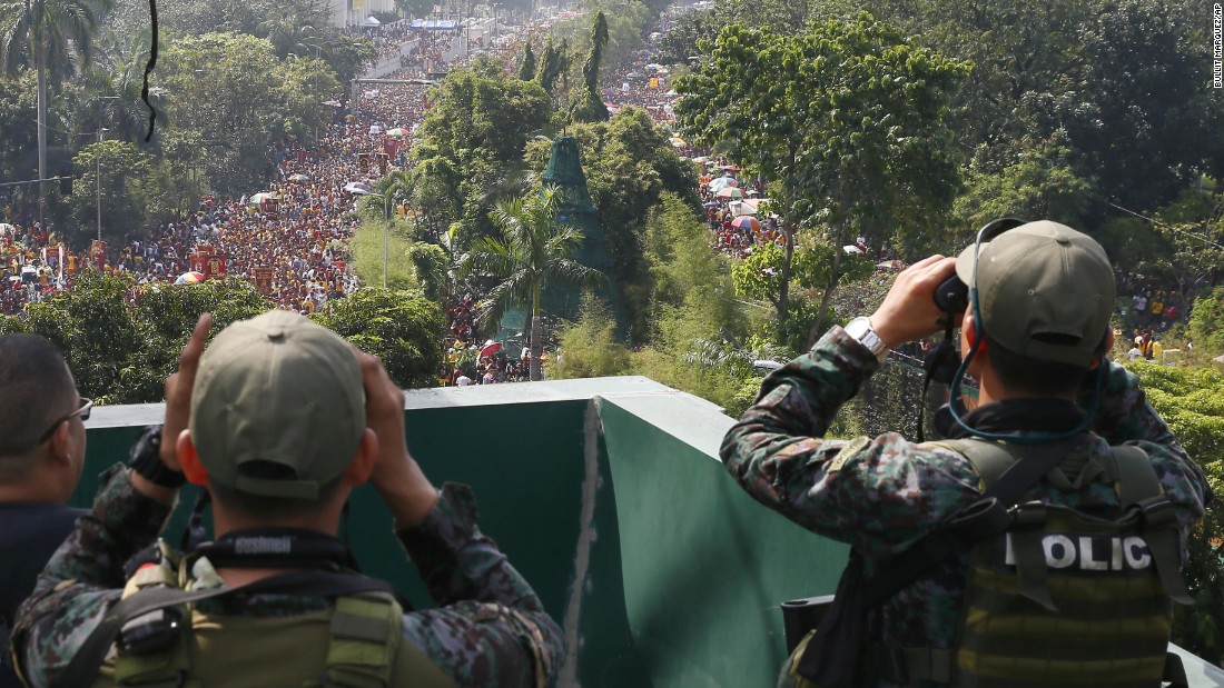 Philippine National Police Special Action Forces scan the route as Filipino Roman Catholic devotees carry the Black Nazarene on January 9 in Manila, Philippines.
