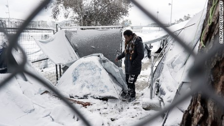 A migrant stands next to a snow-covered tent at the Moria hotspot on the island of Lesbos , following heavy snowfalls on January 7, 2017.  The number of migrants arriving in Europe by two main sea routes in 2016 plunged by almost two-thirds to 364,000 compared with the previous year, EU border agency Frontex said Friday. Frontex pointed to an EU border deal with Turkey which came into effect in March as having paved the way to a massive decline in the arrival of Syrian refugees and other migrants in Greece.  / AFP / STR        (Photo credit should read STR/AFP/Getty Images)