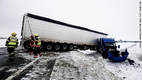 Firefighters help remove a jackknifed semi Tuesday in Hampton Township, Michigan.