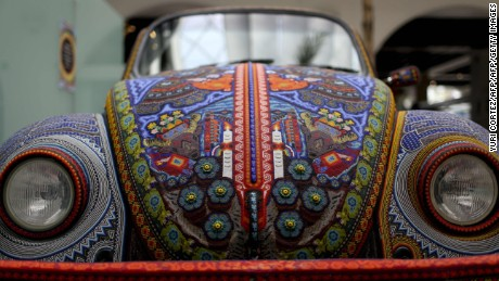 "The ""Vochol"", a 1990 Volkswagen Beetle decorated by members of Mexican Huichol indigenous group with 2,277,000 chaquiras beads, is exhibited at the Folk Art Museum in Mexico City on July 15, 2016.   The Vochol has been exhibited in several museums of the United States, Europe, Asia and South America since 2010. / AFP / YURI CORTEZ        (Photo credit should read YURI CORTEZ/AFP/Getty Images)"