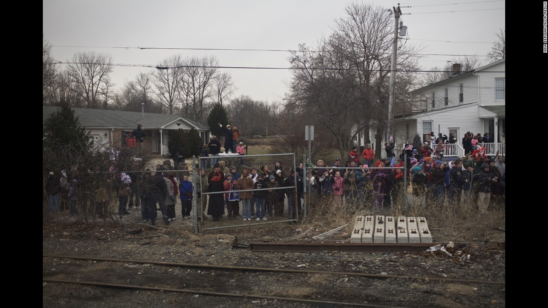 A crowd of people watches a train carrying President-elect Barack Obama to Washington on January 17, 2009. He was on a whistle-stop train tour three days before his inauguration, and photographer Nina Berman was on board.