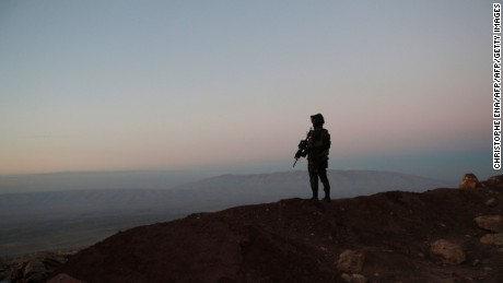 A Kurdish Peshmerga soldier is silhouetted while French President visits a military outpost on the outskirts of the northern city of Mosul, on January 2, 2017.  Western support for military action against Islamic State jihadists is key to preventing attacks at home, French President Francois Hollande said in Iraq, where yet another bombing killed dozens. / AFP / POOL / Christophe Ena        (Photo credit should read CHRISTOPHE ENA/AFP/Getty Images)