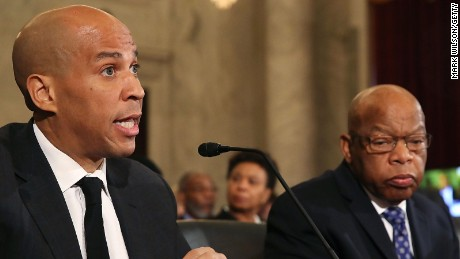 Sen. Cory Booker (L) is flanked by Rep. John Lewis as he reads a statement speaking out against attorney general nominee Jeff Sessions during a Senate Judiciary Committee hearing on Capitol Hill on January 11, 2017.