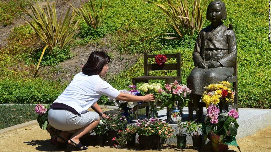 "A woman arranges flowers in front of a ""comfort woman"" statue in Glendale, California."
