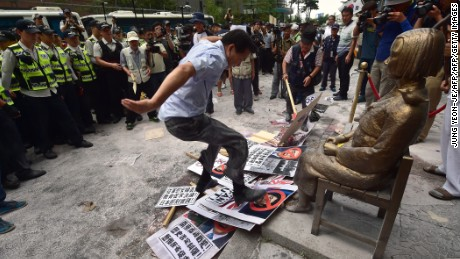 "A South Korean activist (C) tramples down on portraits of Japan's Prime Minister Shinzo Abe in front of a statue (R) of a South Korean teenage girl called the ""peace monument"" for former ""comfort women"" during a rally to mark the 70th anniversary of Japan's surrender in World War II that ended its 1910-45 colonisation of the Korean Peninsula, outside the Japanese embassy in Seoul on August 15, 2015. South Korean President Park Geun-Hye on August 15 urged Japan to match its words with deeds, after a speech by Prime Minister Shinzo Abe expressing remorse over wartime aggression fell short of Seoul's expectations.    AFP PHOTO / JUNG YEON-JE        (Photo credit should read JUNG YEON-JE/AFP/Getty Images)"