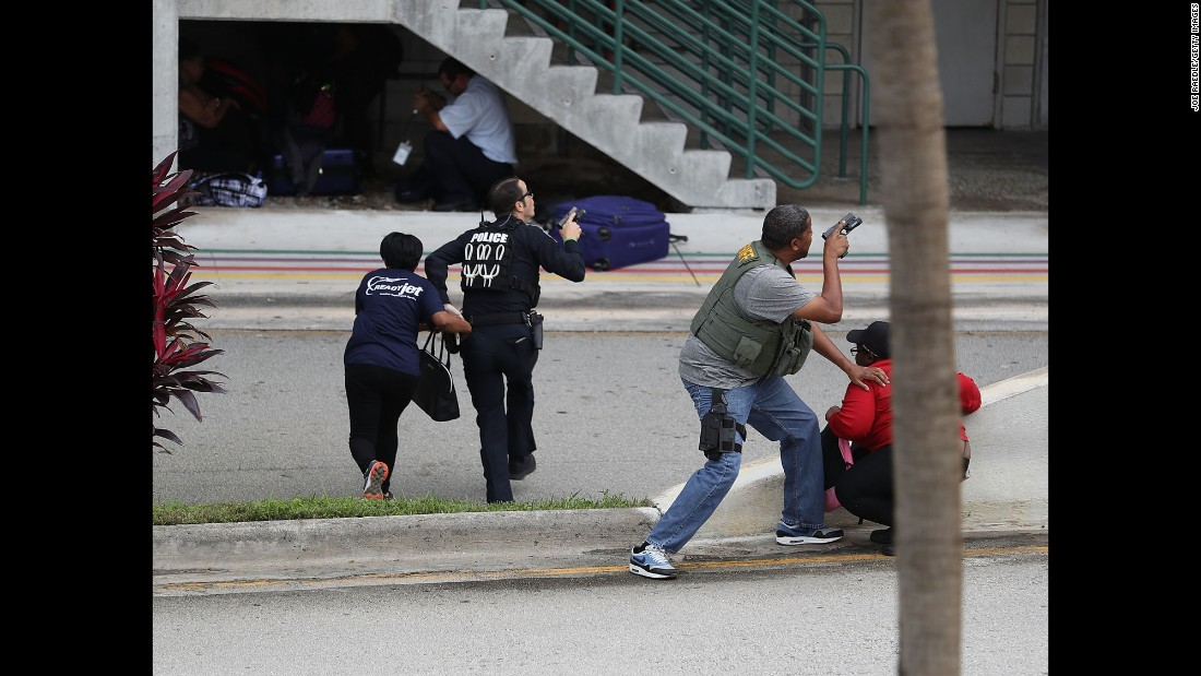 "Police help people seeking cover after a shooting at the airport in Fort Lauderdale, Florida, on Friday, January 6. Five people were killed and eight others were wounded when <a href=""http://www.cnn.com/2017/01/06/us/fort-lauderdale-airport-incident/index.html"" target=""_blank"">a gunman opened fire</a> in the baggage claim area, officials said."