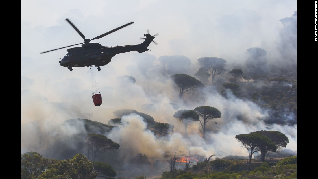 A firefighting helicopter flies over a massive wildfire in Cape Town, South Africa, on Wednesday, January 11.