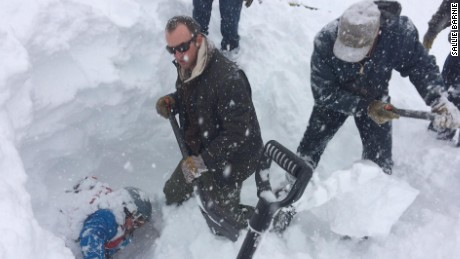Rescuers work to free a skier who was buried under four feet of snow on a Colorado Highway.