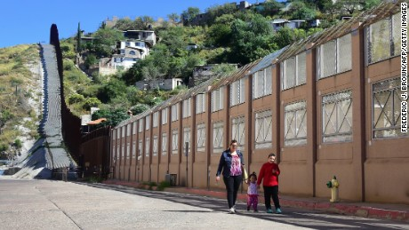 A woman and children walk beside the border wall and fence separating the United States from Mexico on October 11, 2016 in Nogales, Arizona, across the border barrier from Nogales, Sonora.