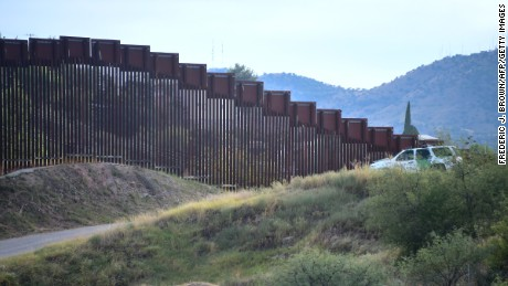 A US Border Patrol vehicle parks beside a section of the US-Mexico border fence in Nogales, Arizona on October 12, 2016, across from Nogales, state of Sonora, Mexico.
