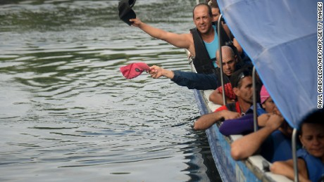 Cuban and Haitians migrants get into a boat to be taken from Turbo to Capurgana, both in the Caribbean Gulf of Uraba in northwestern Colombia, to illegally cross to Panama through the jungle, on August 6, 2016.  Hundreds of Cubans stranded in northwest Colombia have been left facing deportation after the government adopted emergency measures against illegal migration following a massive US-bound influx. Colombia has adopted emergency measures against illegal migration, which include plans to deport thousands of migrants as well as reinforcing its borders. / AFP / RAUL ARBOLEDA        (Photo credit should read RAUL ARBOLEDA/AFP/Getty Images)