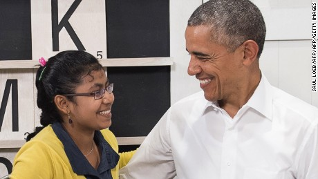 US President Barack Obama smiles with a 16-year-old refugee girl from Myanmar that was subjected to human trafficking and will now be moving to the United States, following a tour of the Dignity for Children Foundation in Kuala Lumpur on November 21, 2015 on the sidelines of his participation in the Association of Southeast Asian Nations (ASEAN) Summit. The Foundation serves more than 1,000 poor and vulnerable children, many of them refugees, in a specialized learning environment to help develop children academically and socially to empower them to become productive members of society.  Obama and his counterparts from China, India, Japan and elsewhere are meeting in Kuala Lumpur for two days of talks hosted by the 10-country ASEAN.   AFP PHOTO / SAUL LOEB        (Photo credit should read SAUL LOEB/AFP/Getty Images)