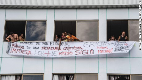 A group of Cubans hang a banner with inscriptions against the Cuban government from an abandoned building in Paso canoas, 590 km west of San Jose, on the border with Panama on April 14, 2016. Police was deployed after more than 1,000 migrants, most of them Cubans, thronged and then stormed across Panama's border into Costa Rica Wednesday in a desperate bid to reach the United States. / AFP / Ezequiel Becerra        (Photo credit should read EZEQUIEL BECERRA/AFP/Getty Images)