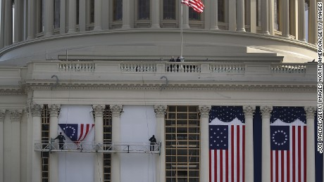 Workers hang an early version of the American flag on the U.S. Capitol to be used as part of the backdrop to the presidential inauguration for President elect Donald Trump as he prepares to take the reins of power next week on January 13, 2017 in Washington, DC.