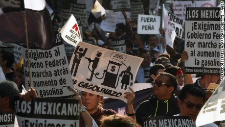 People protest demanding the resignation of President Enrique Pena Nieto, after he did not signal any backpedaling on the government's unpopular decision to increase gasoline prices by up to 20.1 percent in Mexico City on January 9, 2017.  Violent demonstrations and looting in Mexico over the sharp increase in gasoline prices left three people dead and more than 1,500 under arrest last week. Mexico's government, business leaders and agricultural groups agreed on Monday to prevent increases in the cost of basic goods after a gasoline price hike sparked daily and sometimes violent protests. / AFP / ALFREDO ESTRELLA        (Photo credit should read ALFREDO ESTRELLA/AFP/Getty Images)