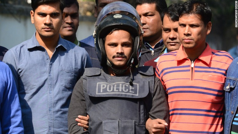 Bangladesh police escort suspect Jahangir Alam, in body armor, in Dhaka on Saturday after his arrest.