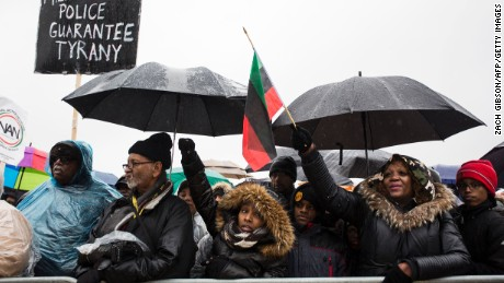 "Demonstrators listen to speeches during a rally following the ""We Shall not be Moved"" march organized by the National Action Network January 14, 2017 in Washington, D.C."