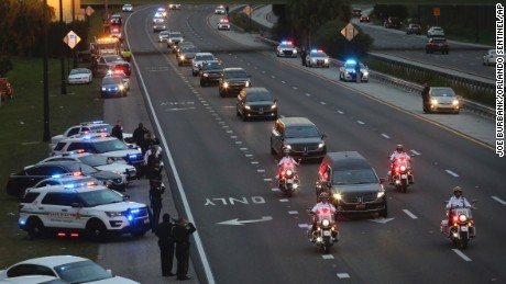 Officers parked on the side of S.R. 408 salute as the procession escorting the hearse of slain Orlando Police Lt. Debra Clayton on Saturday