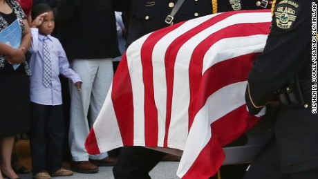 A young boy, left, salutes as the flag-draped casket is carried during funeral services for Orlando Police Lt.  Debra Clayton at the First Baptist Church in Orlando. Clayton was posthumously promoted to  the rank of lieutenant.