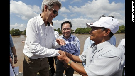 U.S. Secretary of State John Kerry, left, shakes hands with Vo Van Tam, 70, right, who was a member of the former Viet Cong guerrilla, who took part in the attack on Kerry's Swift Boat in February 28, 1969, while on a tour of the region Saturday, January 14, in the Mekong River Delta, Vietnam.