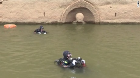 An underwater archeology team is investigating both the ancient town and the statue.