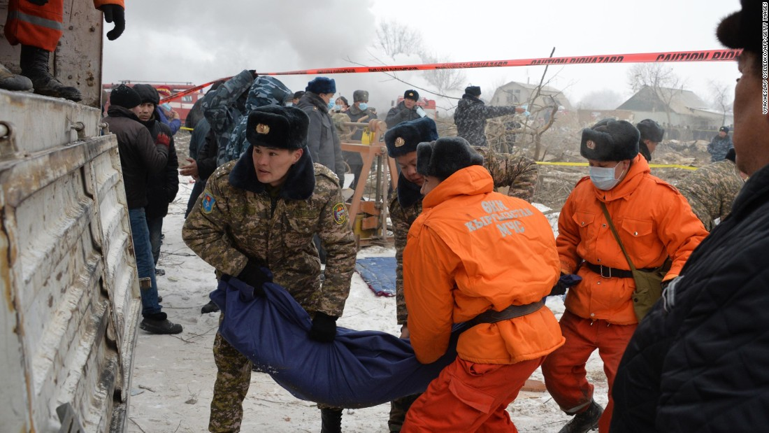 Rescuers carry the body of a victim at the crash site on January 16. At least 37 people were killed, and the death toll is likely to rise, according to a statement from Kyrgyzstan's Ministry of Emergency Situations.